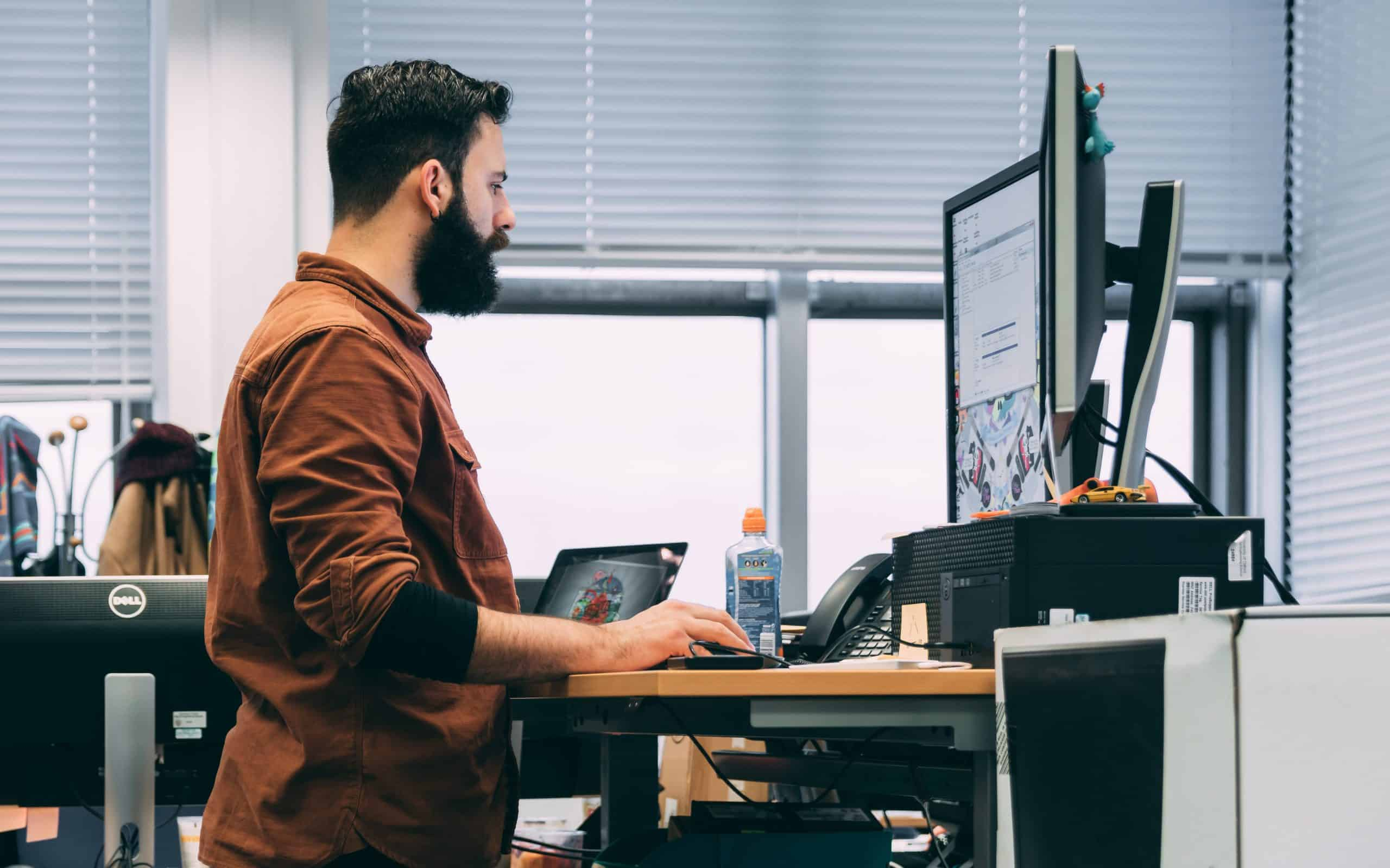 man using standing desk edited scaled