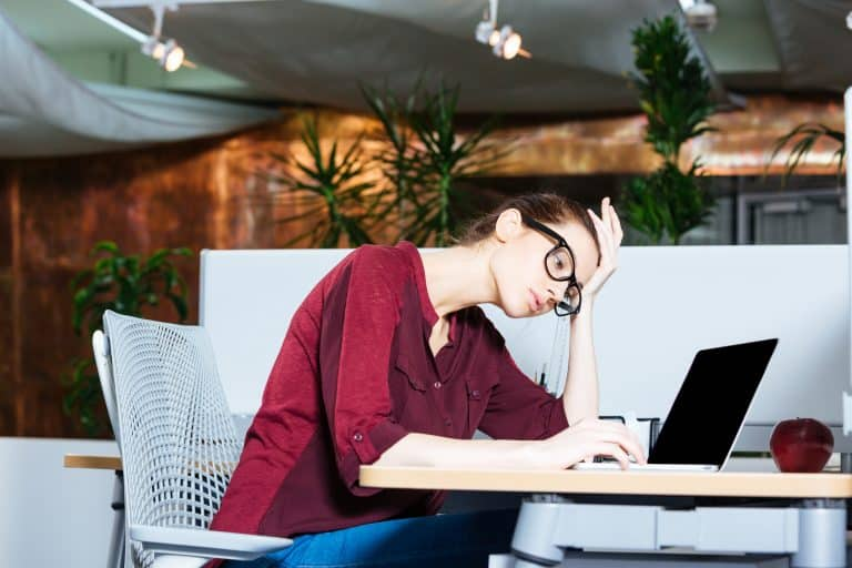 Business woman working with laptop and having headache in office